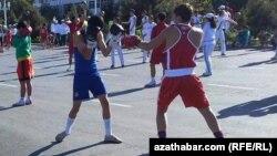 Türkmenistanda geçirilýän sport çäreleriniň birinde iki sportsmeniň türgenleşip duran pursady.