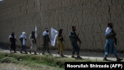 FILE: Afghan Taliban militants walk in the outskirts of the eastern city of Jalalabad.