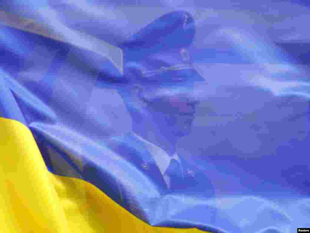 An honor guard is seen through the Ukrainian flag during a ceremony welcoming Sri Lankan President Mahinda Rajapaksa to Kyiv on June 30. Photo by Gleb Garanich for Reuters