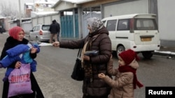 Сторонница ПИВТ раздает предвыборный листовки в Душанбе. 26 февраля 2015 года.