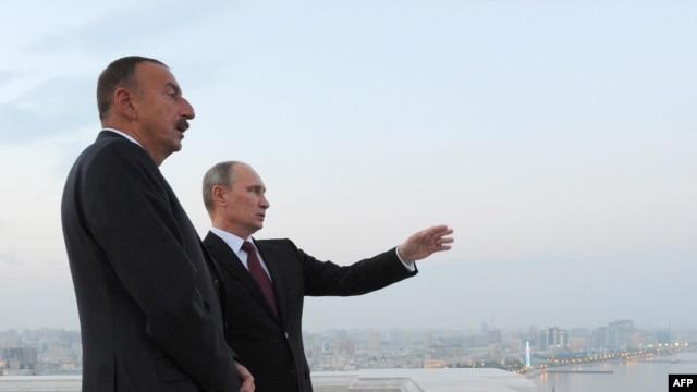 Azerbaijan -- Russia's President Vladimir Putin (L) and his Azerbaijani counterpart Ilham Aliyev (R) speak as they walk in Baku, on August 13, 2013.