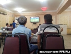 Türkmenistanda kafede telewizora tomaşa edýän adamlar