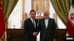 China's Wang Yi is welcomed by Iran's Mohammad Javad Zarif in Tehran on February 15.