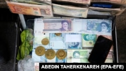 Iranian bills stacked in a briefcase with a few gold coins in a currency exchange service in Tehran, Iran, 22 June 2020.