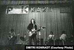"""Mihail Vasziljevics """"Mike"""" Naumenko és együttese, a Zoopark játszik 1983-ban a Leningrádi Rock Klubban. Naumenko, aki csípősen szatirikus szövegeiről volt ismert, jelentős szerepet játszott a nyugati zenei tradíció oroszországi adaptálásában. Manapság is az ország egyik legbefolyásosabb szövegírójának tartják, annak ellenére, hogy 1991-ben, 36 évesen agyvérzésben meghalt."""