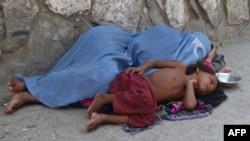 Баласымен көлеңкеде демалып жатқан әйел. Джалалабад, 8 шілде 2012 жыл
