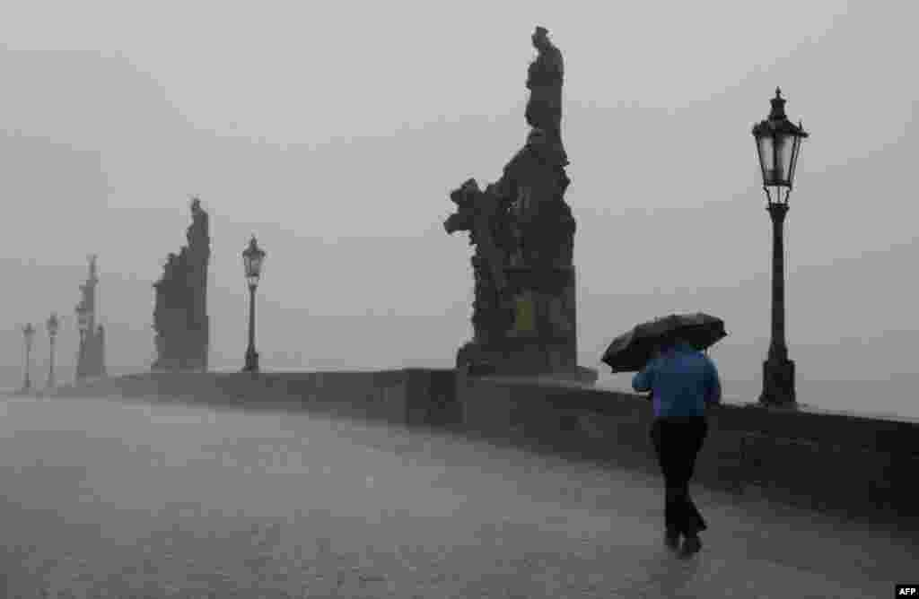 A man with an umbrella crosses the Charles Bridge during a heavy rainfall in Prague. (AFP/Michael Cizek)