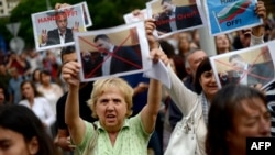 Demonstrators hold aloft pictures of Delyan Peevski at a rally in Sofia. (file photo)