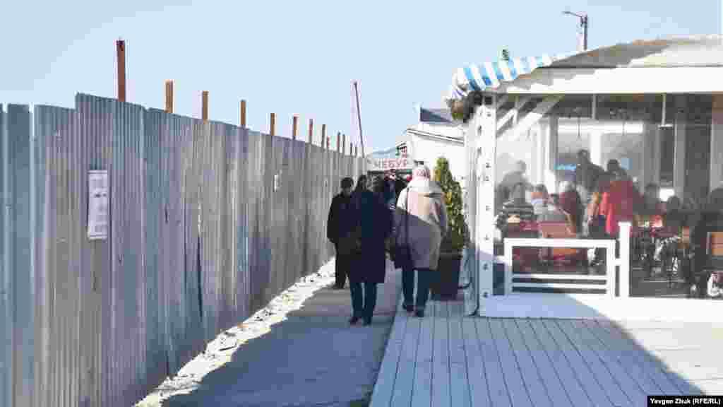 Прохід до моря крізь вузький коридор між будівельним парканом і торговими павільйонами