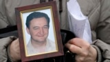 A portrait of lawyer Sergei Magnitsky, who died in jail, is held by his mother, Natalia Magnitskaya, in Moscow in November 2009.