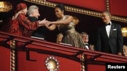 Michelle Obama salutînd în decembrie 2012 invitații Centrului Kennedy, balerina Natalia Makarova și actorul Dustin Hoffman