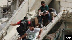Syrian men remove a baby from the rubble of a destroyed building following a reported air strike in the Al-Qatarji neighborhood of the northern city of Aleppo on September 21.