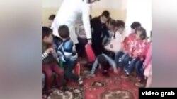 Воспитательница джизакского детсада бьет детей файловой папкой. Кадр из видеозаписи.