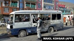 A security personnel visits the site of a blast in Kabul on March 18 that hit a bus carrying government employees.