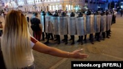 A woman gestures toward riot police in the city of Homel on August 10.