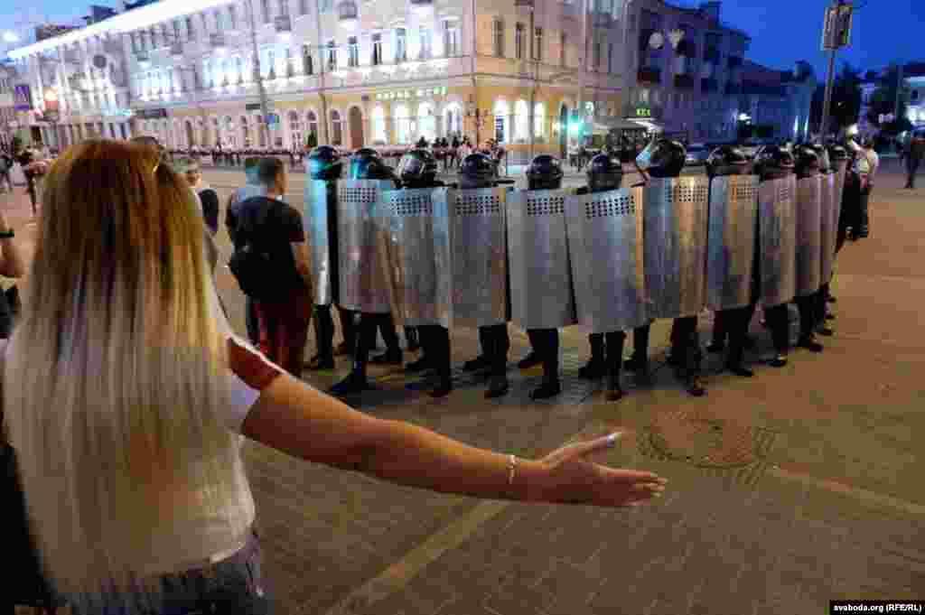 O femeie gesticulează în fața forțelor de ordine în Homel, în 10 august.