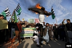 Supporters of the Rah-e-Haq party burn an effigy of Iran, Israel, and the United States during a rally in favor of the execution of Shi'ite cleric Nimr al-Nimr in Peshawar in January 2016.