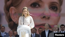 Yevhenia Tymoshenko, daughter of Yulia Tymoshenko, addresses supporters of opposition parties in front of a screen displaying a picture of her jailed mother at a May 12 rally in Kyiv.