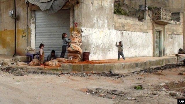 Children hide behind sandbags on the street in the central Syrian town of Rastan, near Homs.