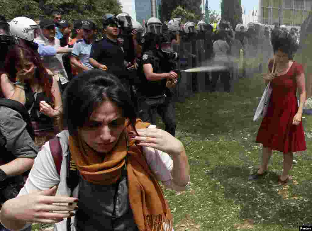 A Turkish riot policeman uses tear gas point-blank against one woman as people protest in Istanbul's Taksim Square against a city development project. (Reuters/Osman Orsal)