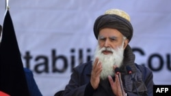 Afghan Afghan Islamist leader Abdul Rab Rasul Sayyaf addresses the gathering on December 18.
