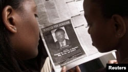 "FILE PHOTO: Readers look at a newspaper June 12, 2002 in Nairobi carrying the photograph of Rwandan Felicien Kabuga wanted by the United States. The United States published a ""wanted"" photograph in Kenyan newspapers of the businessman accused of helping f"