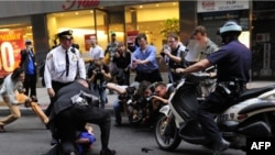 Photographers gather as an Occupy Wall Street protester is detained near Zuccotti Park in New York City on October 14.