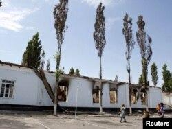 Жители Оша проходят мимо сгоревшей во время конфликта школы. 26 июня 2010 года.