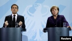 German Chancellor Angela Merkel (right) and French President Nicolas Sarkozy address a news conference following their talks at the Chancellery in Berlin on January 9.