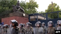 Iranian riot police stand guard outside the British Embassy in Tehran as hard-line students demonstrate.