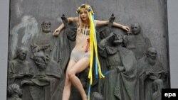 Активістка Femen Анна Алляйн вилізла на пам'ятник Київському князеві Володимиру із написом на грудях «Путін вбиває». Київ, 27 липня 2017 року