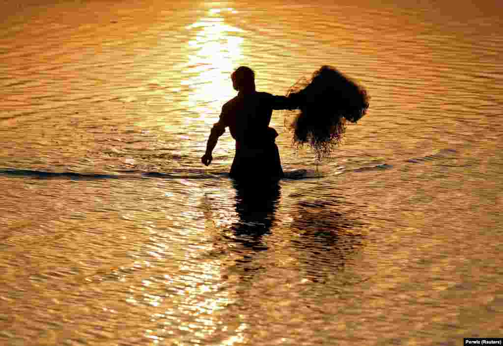 An Afghan man tries to catch fish during sunset by a river on the outskirts of Jalalabad on October 3. (Reuters/Parwiz)