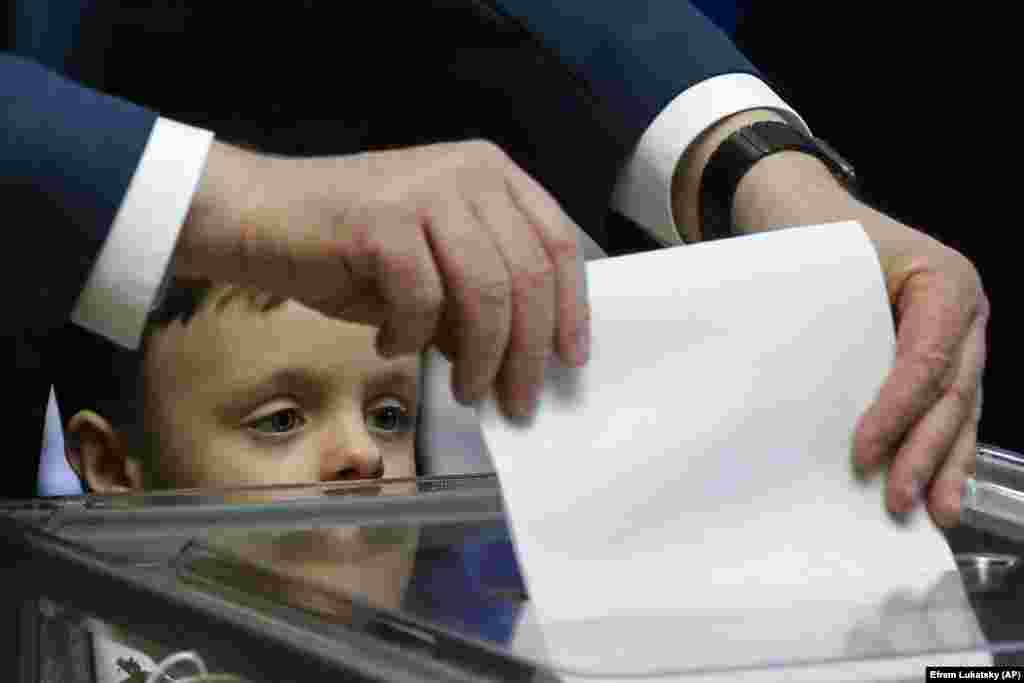 Ukrainian President Petro Poroshenko casts his ballot as his grandson, Petro, looks on, at a polling station in Kyiv. (AP/Efrem Lukatsky)