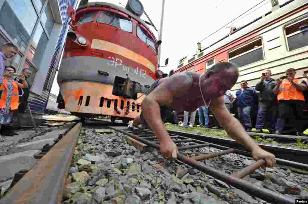 Athlete and powerlifter Ivan Savkin pulls a train with several carriages, weighing a combined 120 tons, in the Russian Far East city of Vladivostok. (Reuters/Yuri Maltsev)