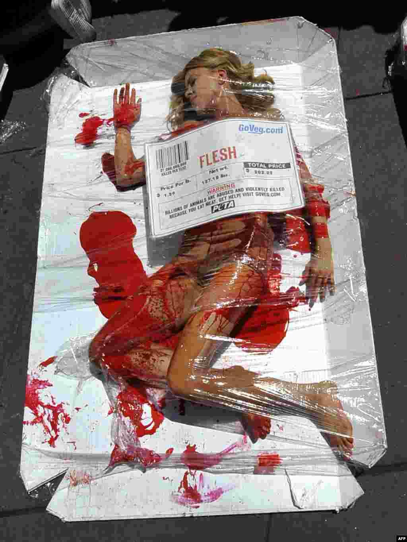 Інсталяція активістів руху «Люди за етичне поводження з тваринами» (PETA) відтворює вміст типового пакету м'яса. Напис на плакаті-ціннику: «Мільярди тварин піддають насильству і жорстоко вбивають, тому що Ви їсте м'ясо!». Таймс-сквер у Нью-Йорку, 27 липня. Photo by Timothy A. Clary for AFP