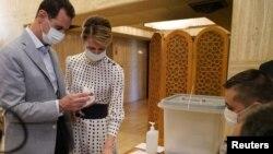 Сирия президенті Башар Асад (сол жақта) және әйелі Асма.
