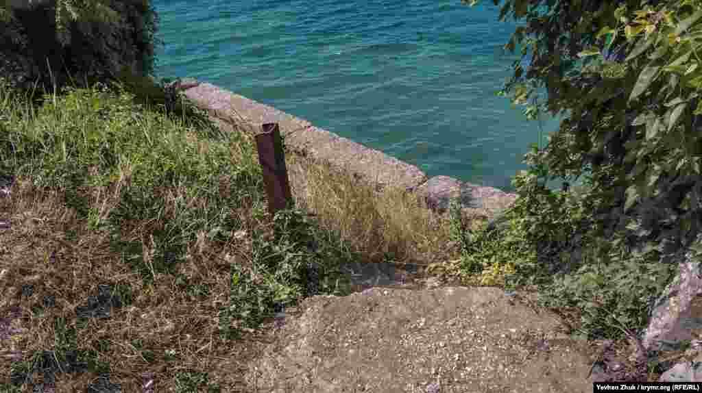 Піщаний пляж розташований поруч із російською військовою частиною. Спуститися на нього можна тільки дома необладнаними кам'янистими стежками, де з грунту стирчать шматки металевої арматури