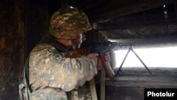 Armenia - A soldier with a machine gun at an Armenian army outpost on the border with Azerbaijan, 27Nov2013.