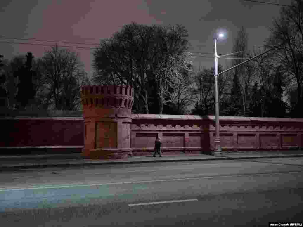 Женщина проходит мимо стен Новодевичьего кладбища после пяти часов вечера, когда кладбищенские ворота закрываются, и только патруль кладбищенской охраны нарушает тишину этого места.