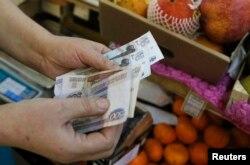 Базардағы сатушы рубль санап жатыр. Мәскеу, 3 наурыз 2014 жыл.