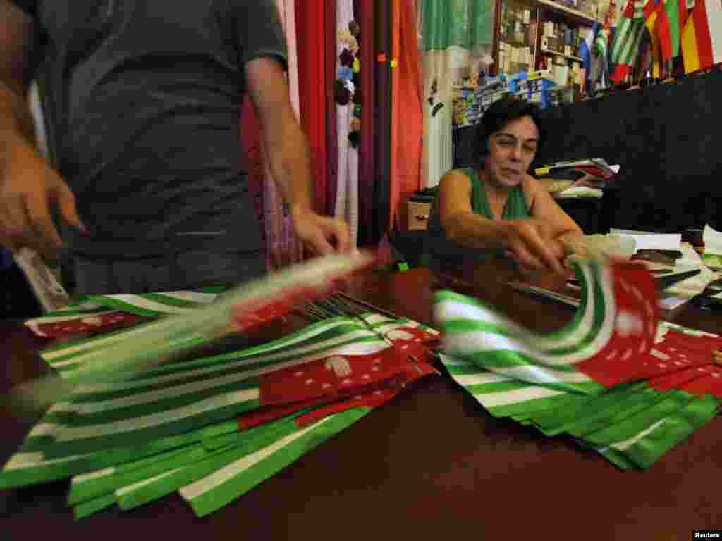 Workers in a shop prepare flags ahead of an election in Sukhumi, capital of the breakaway Georgian region of Abkhazia, on August 25. Photo by Sergei Karpov for Reuters