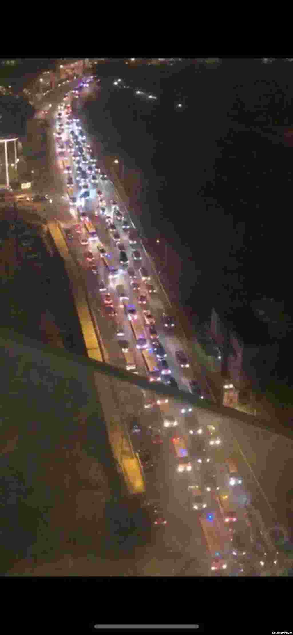 Полицейские машины направляются в сторонууниверситета PolyU. Фото снято в 20 часов по местному времени 18 ноября 2019 года из окна студенческого общежития.