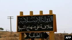 FILE: An Islamic State group banner showing an arrow towards the town of Tabqa in Syria.