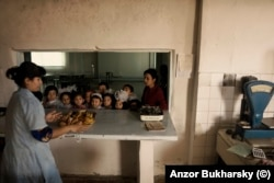 Schoolchildren being served a lunch of sandwiches and deep-fried bread at a school in Bukhara in 2010