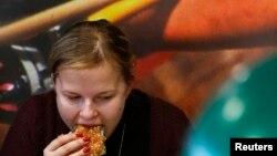 Женщина ест бургер в ресторане фастфуда. Иллюстративное фото.
