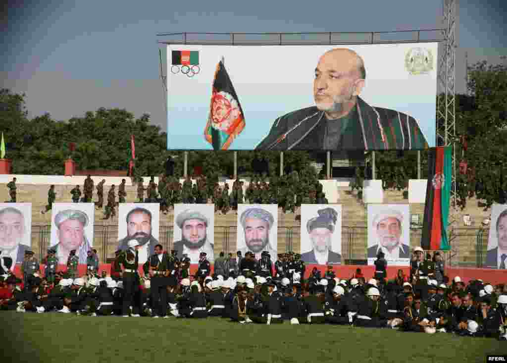 Afghan officers and military academy cadets sit in front of large portraits of President Hamid Karzai and commanders who were killed during the Soviet invasion in the 1980s. Photo by RFE/RL