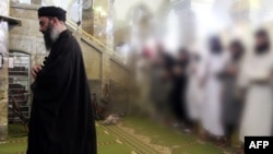 A video grab allegedly shows the leader of the Islamic State (IS) jihadist group, Abu Bakr al-Baghdadi, leading prayers next to machine guns with Muslim worshippers behind him.