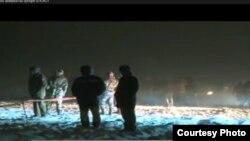 АН-72 ұшағы құлаған жерде жүрген полиция қызметкерлері. 24kz телеарнасының апат туралы сюжетінен алынған скриншот. Оңтүстік Қазақстан облысы, 25 желтоқсан 2012 жыл.
