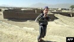 د کوټې ښار په څنډو کې د افغان کډوالو په یوه خړپړ کېمپ کې یو افغان کډوال غوټه پر شا کور ته روان دی