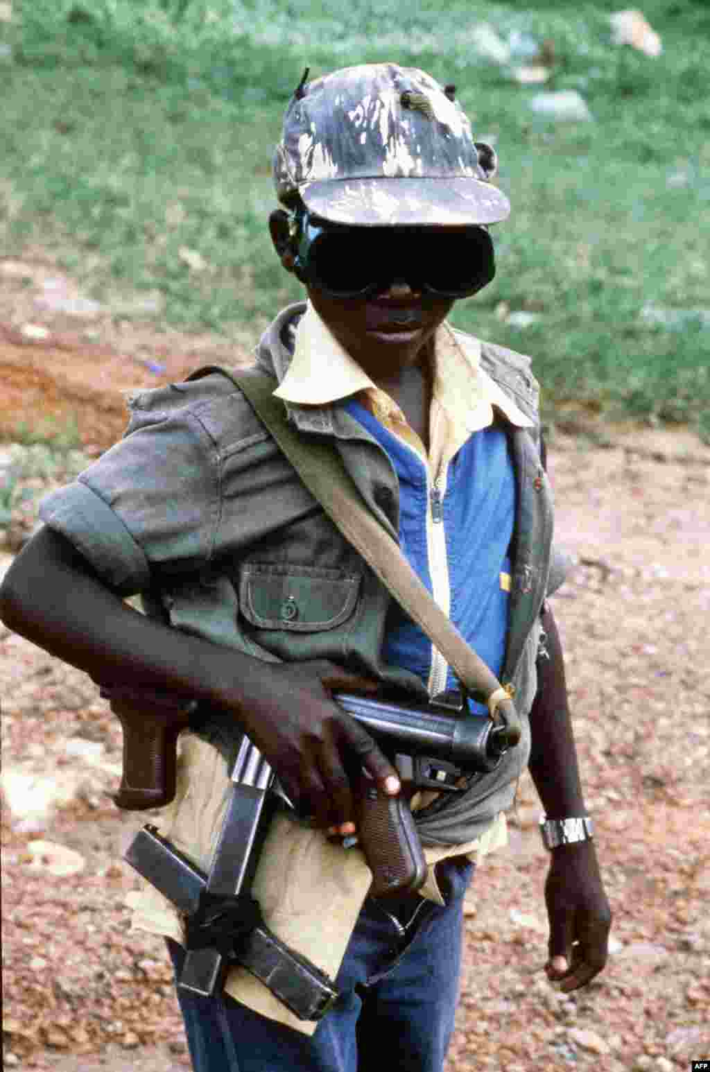 Не менее 30 тысяч детей из Уганды не пойдут в школу в этом году – их используют в качестве солдат в религиозном конфликте. Похищенным и завербованным мальчикам лидеры разрозненных группировок дают в руки автоматы. Иногда вооружают и девочек, но значительно чаще их используют как секс-рабынь. На фото – маленький боец партизанской группировки Народная армия сопротивления Уганды